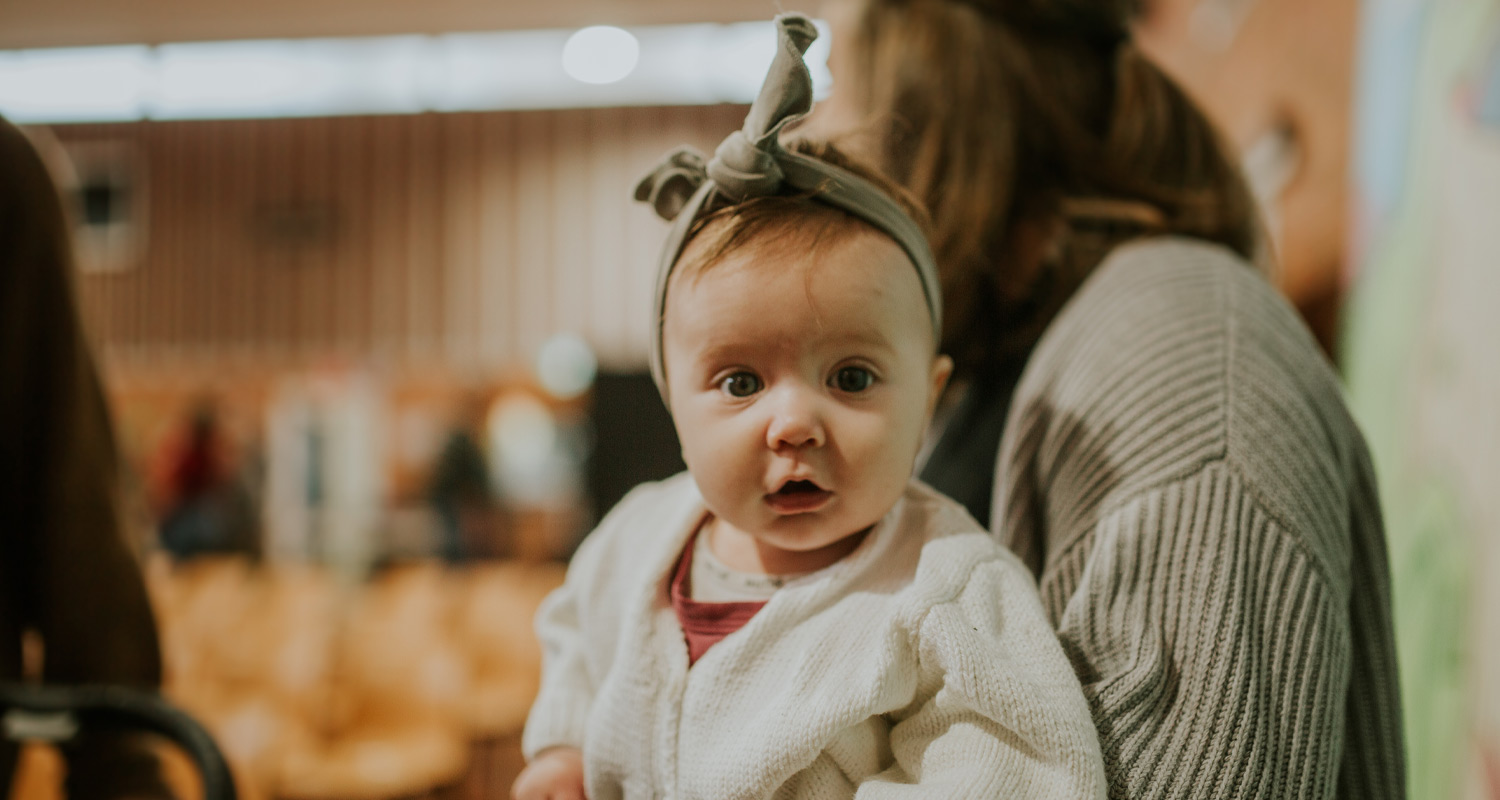Cute baby held by parent for Creche Program